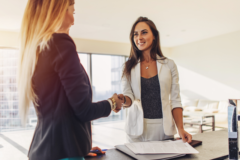 Female customer shaking hands with real estate agent